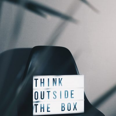 A sign that says think outside the box on a black chair
